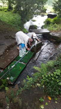water source as part of a bigger shrine in Nishiharamura. Two elder people are washing beans and filling their bottles.